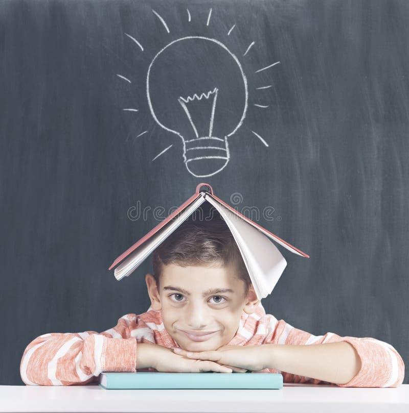 Smart schoolboy posing in front of a blackboard stock photo