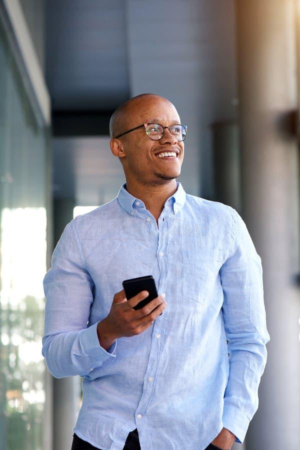 Smart seende afrikansk affärsman som går med mobiltelefonen arkivbilder