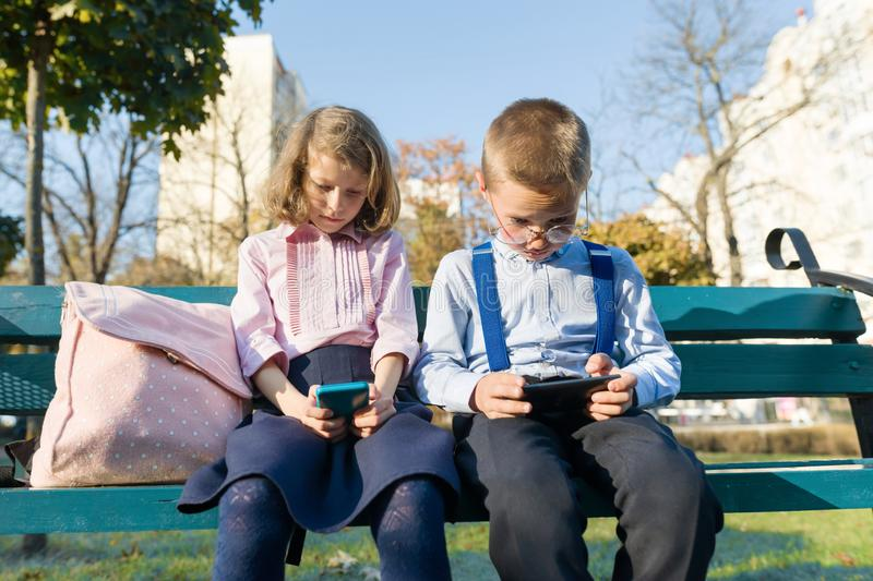 Smart serious children boy and girl are looking into smartphones. On a bench with school backpacks. Background autumn sunny park, golden hour royalty free stock photo