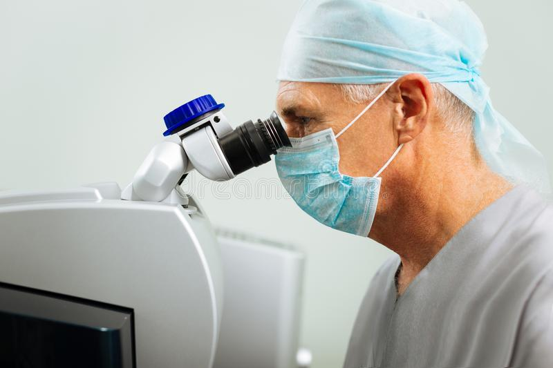 Smart serious doctor looking into the microscope royalty free stock photo