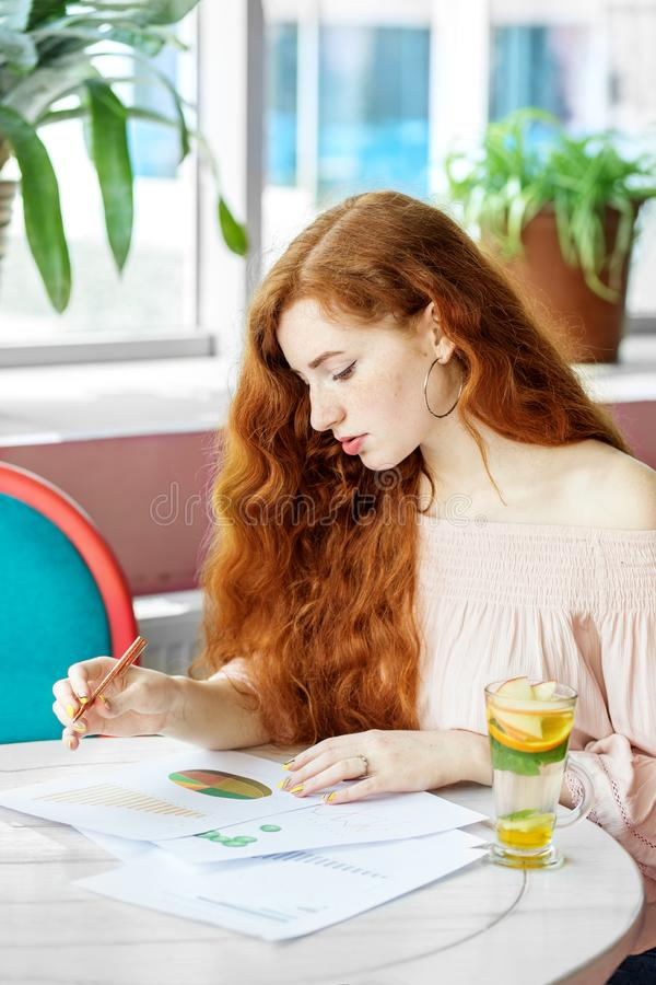 A smart serious woman is making a financial plan. The concept of work, business, education, freelance, lifestyle.  stock photo
