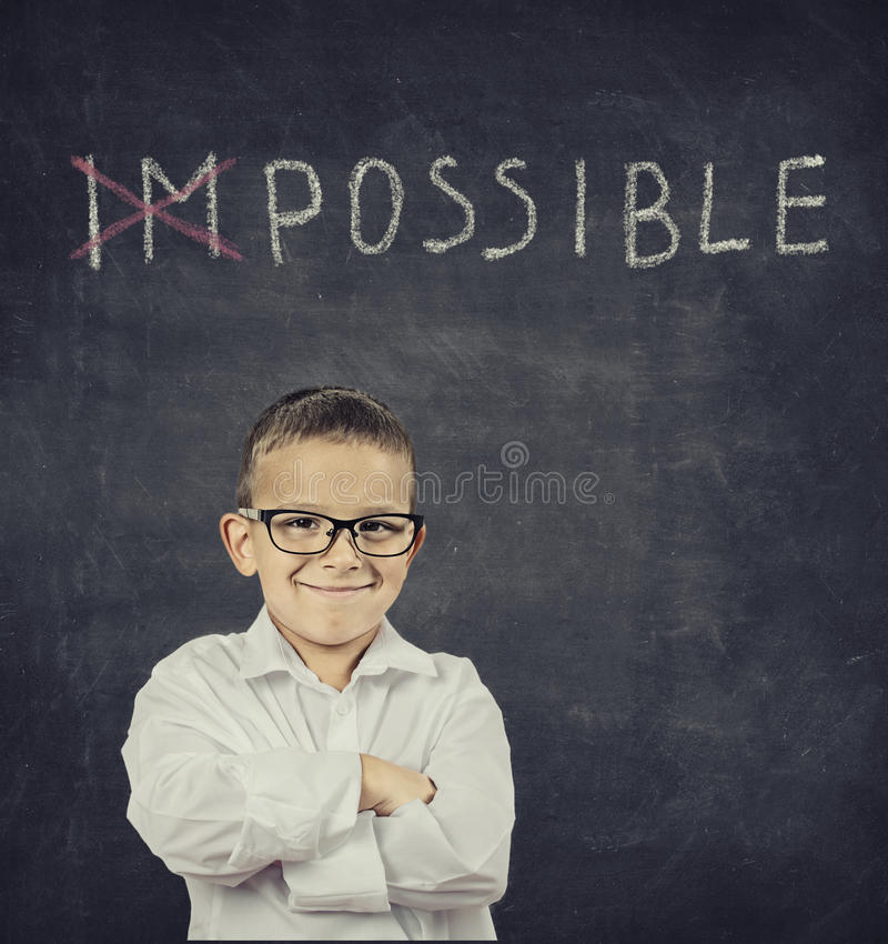 Smart smiling boy standing in front of blackboard. Closeup portrait smart smiling boy standing in front of a blackboard royalty free stock photography