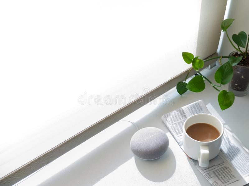 A smart speaker assistant on a window bay with coffee. royalty free stock image