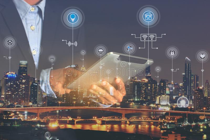 Smart stad eller internet av saker IoT, dubbel exponering av affärsmanhänder som rymmer den digitala minnestavlan med symbolen el royaltyfri fotografi