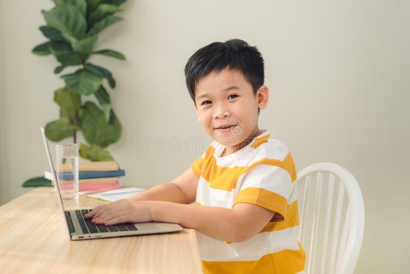 Smart stil för asiatiska tonåringar som skriver och använder en bärbar dator som studerar onlinekurser fotografering för bildbyråer