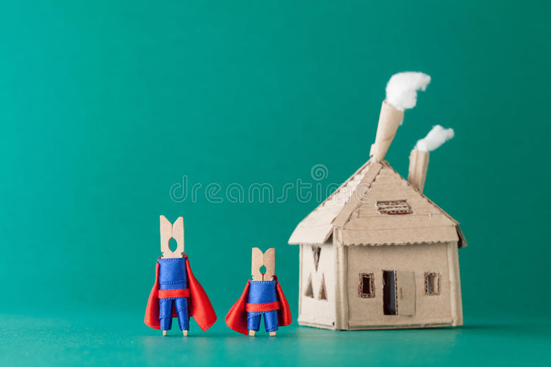 Smart and strong clothespin superheroes cardboard house. Big small super team characters on green background. soft. Smart and strong clothespin superheroes and royalty free stock photography
