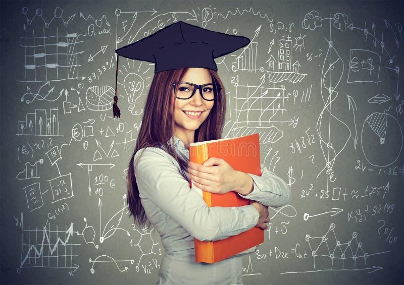 Smart student with graduation cap over math science formulas blackboard royalty free stock photo