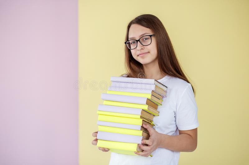 A smart teen girl holds many different books. A child with glasses. Concept of education, hobby, study and world book day royalty free stock photography