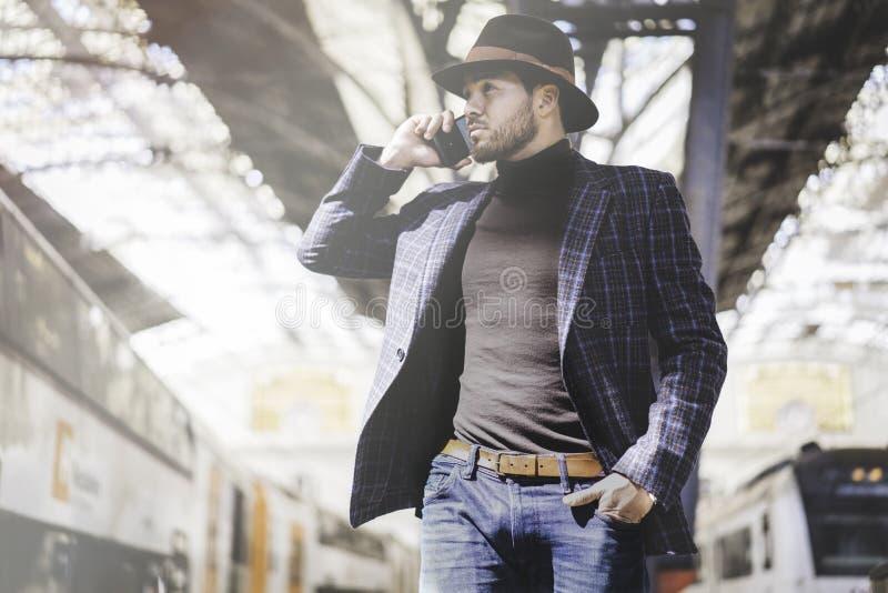 Smart telefon för attraktivt stilfullt ungt latinamerikanskt maninnehav, i hans hand och att kalla medan honom som står på järnvä fotografering för bildbyråer