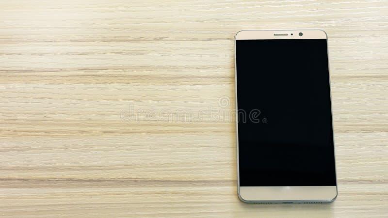 Smart telefon för bild på den vita trätabellen royaltyfri bild