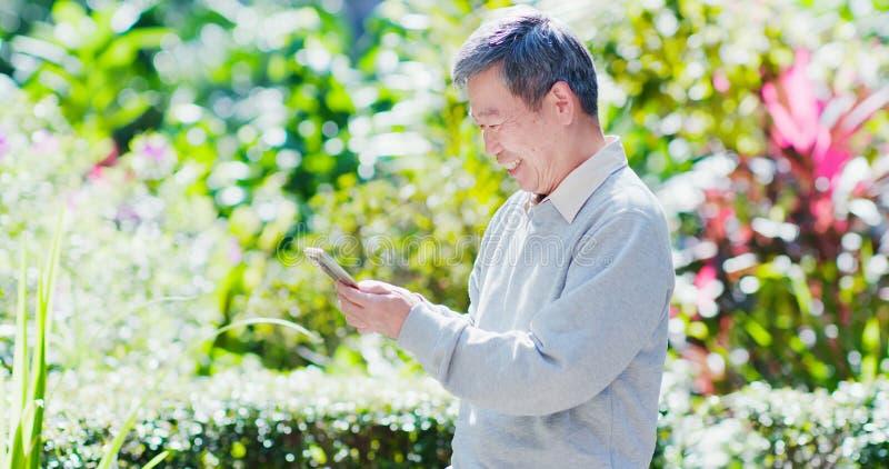 Smart telefon för gamal manbruk royaltyfri bild
