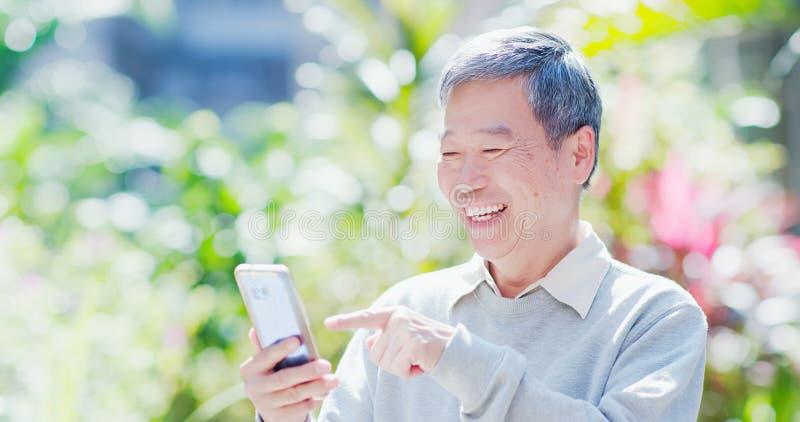 Smart telefon för gamal manbruk royaltyfri fotografi