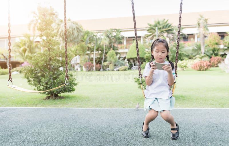 Smart telefon för gullig lek för flickastudent på gunga royaltyfria foton