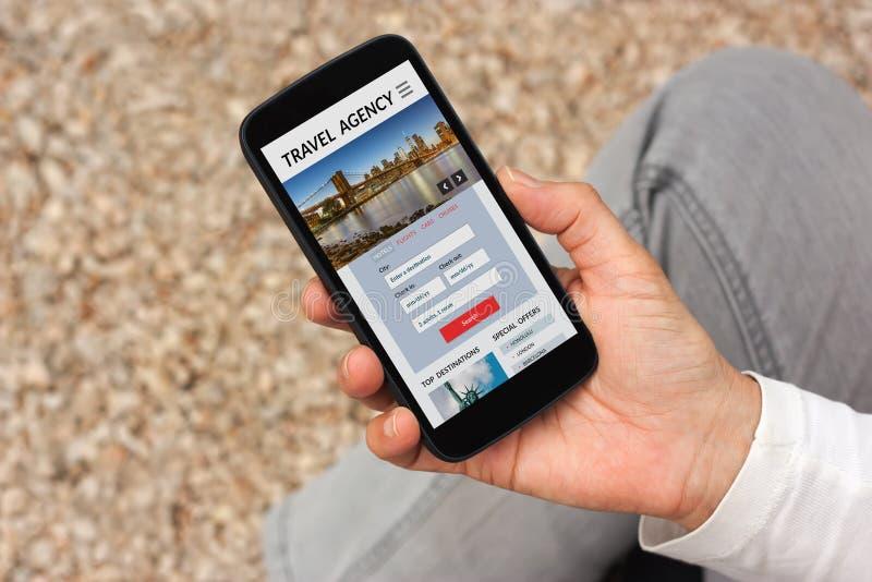 Smart telefon för handinnehav med begrepp för loppbyrå på skärmen royaltyfria bilder