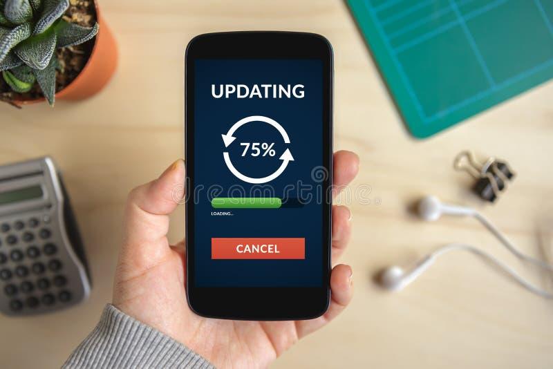 Smart telefon för handinnehav med uppdateringbegrepp på skärmen royaltyfri bild