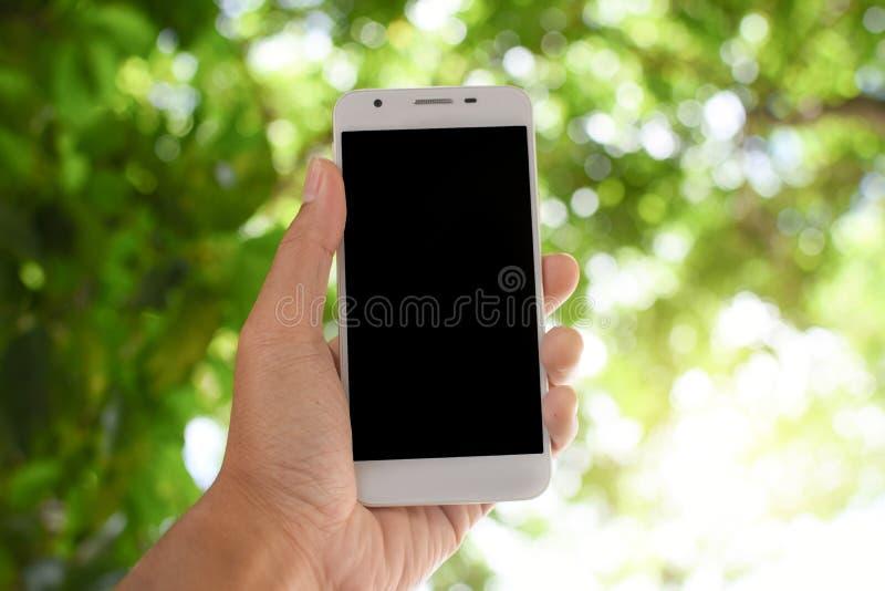 Smart telefon för handinnehav på bokehnaturbakgrund royaltyfria bilder