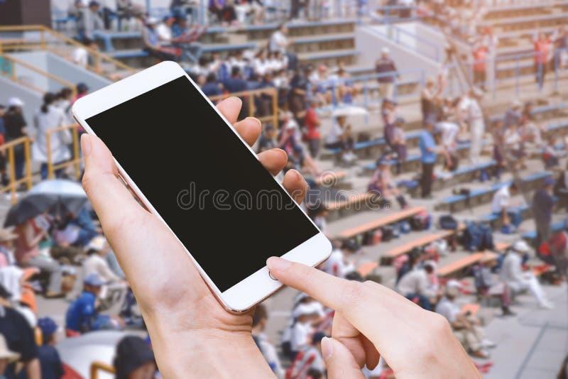 Smart telefon för kvinnahåll och handlagknapp vid handen med den tomma skärmen för annonsering, stadion och åhörarebakgrund, tekn royaltyfri fotografi