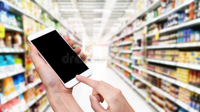 Smart telefon för kvinnahåll och handlagknapp vid handen med den tomma skärmen för annonseringen, oskarp supermarketbakgrund, tek royaltyfri bild