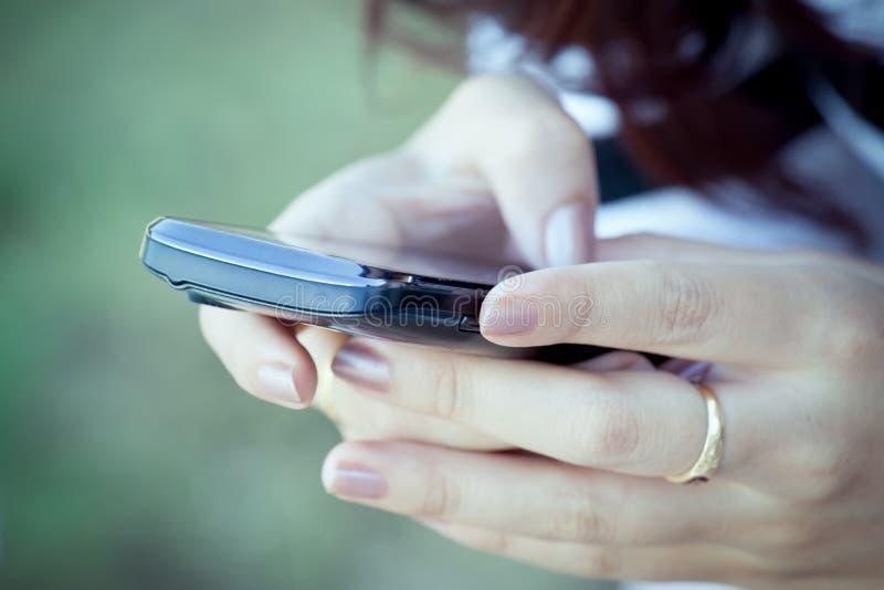 Smart telefon för kvinnahandbruk, minnestavla, mobiltelefon, telefon royaltyfri bild
