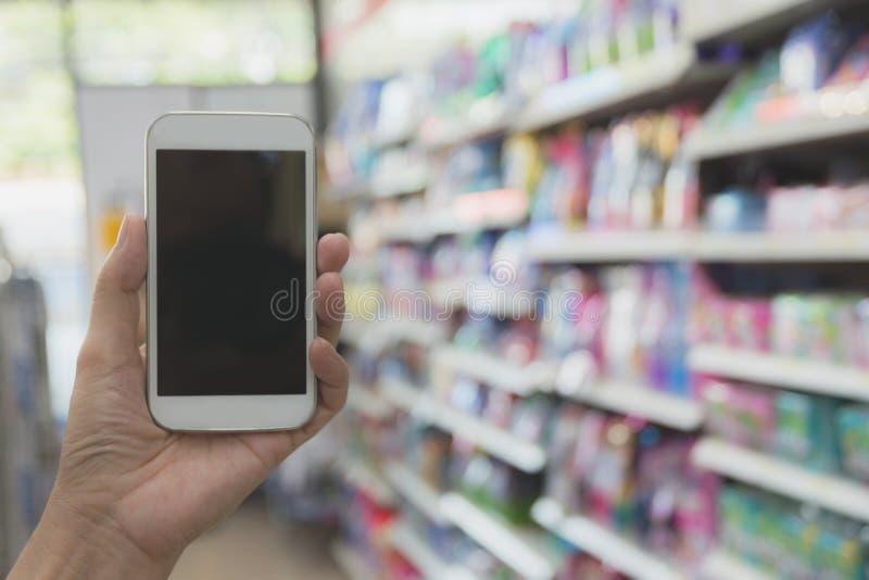 Smart telefon för kvinnahandinnehav i shopping för toppen marknad royaltyfri fotografi