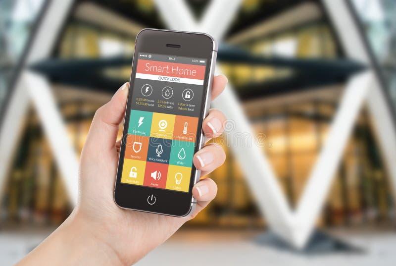 Smart telefon för kvinnlig handinnehavsvart med smart hem- applicatio royaltyfri foto