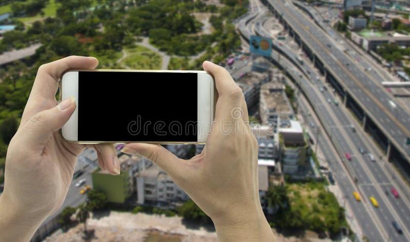 Smart telefon för kvinnligt handinnehav över trafikvägbakgrund arkivfoton