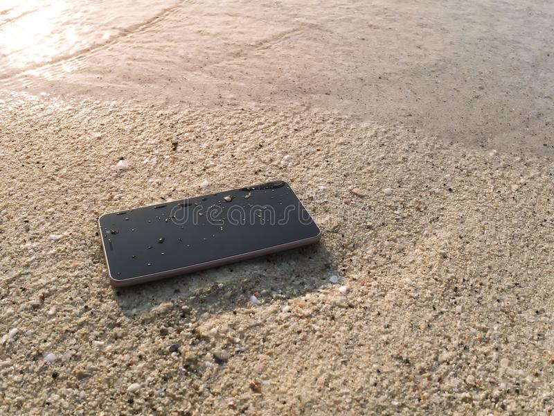 Smart telefon för mobil på den sandiga stranden med mjuka vågor av havsbakgrund Internet av tingbegreppet arkivfoto