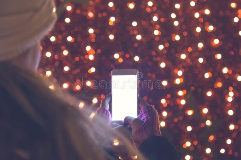Smart telefon för ung kvinnaholding Röd bokeh i bakgrunden arkivfoto