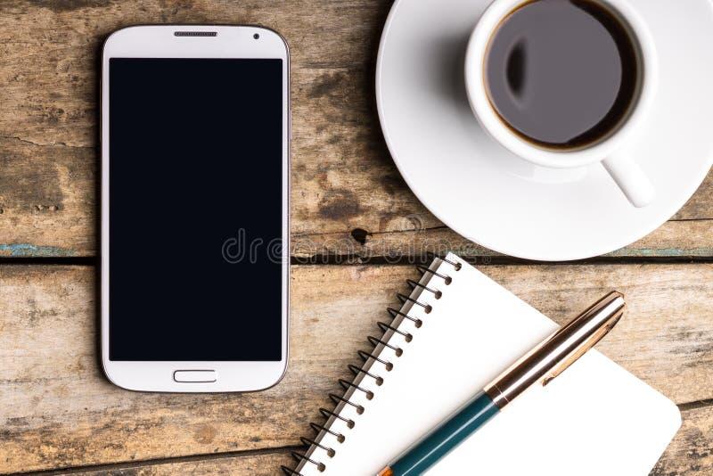 Smart telefon med anteckningsboken och koppen av starkt kaffe arkivbild