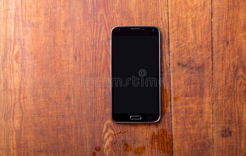 Smart telefon på trätabellbakgrund fotografering för bildbyråer