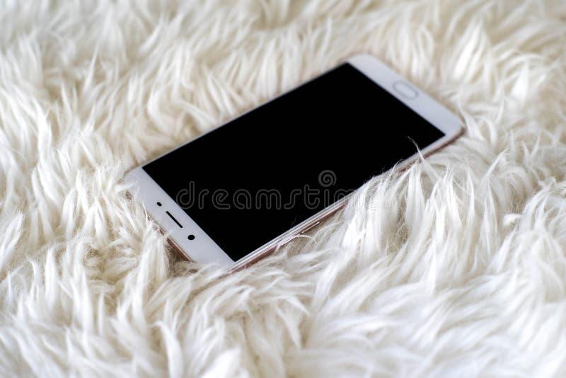 Smart telefon på vit matta royaltyfri bild