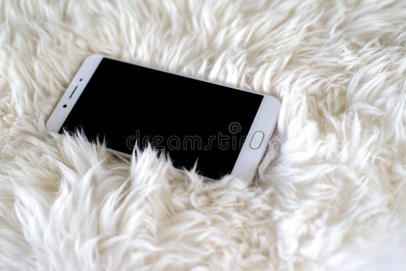Smart telefon på vit matta royaltyfri fotografi