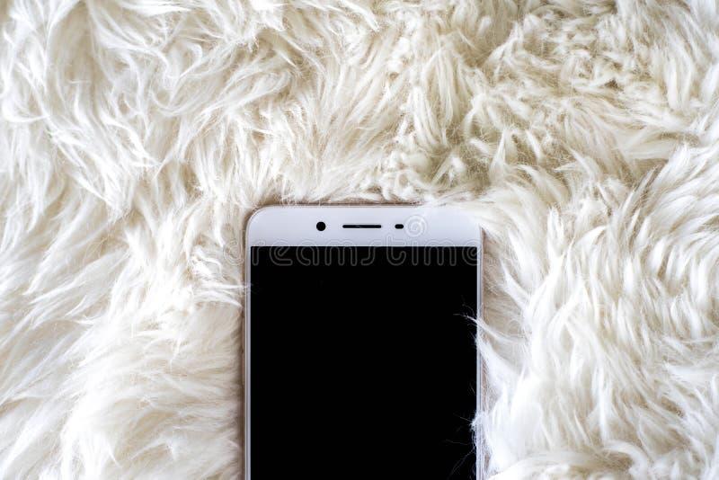 Smart telefon på vit matta royaltyfria foton