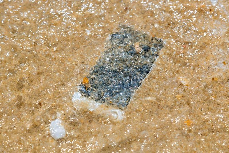Smart telefon som in faller till den sandiga stranden för vatten med vågor av den skadade smarta telefonen för hav royaltyfria bilder
