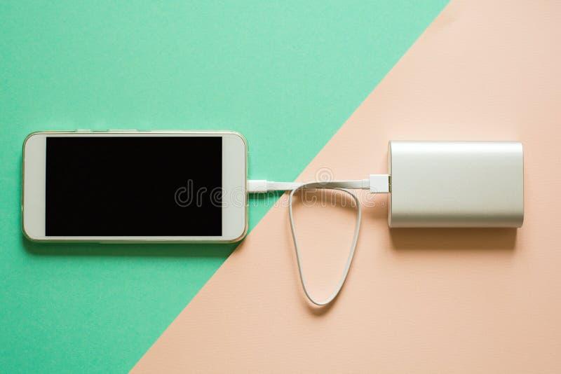 Smart telefon som laddar med maktbanken på pappers- bakgrund Uppladdningbegrepp royaltyfria foton