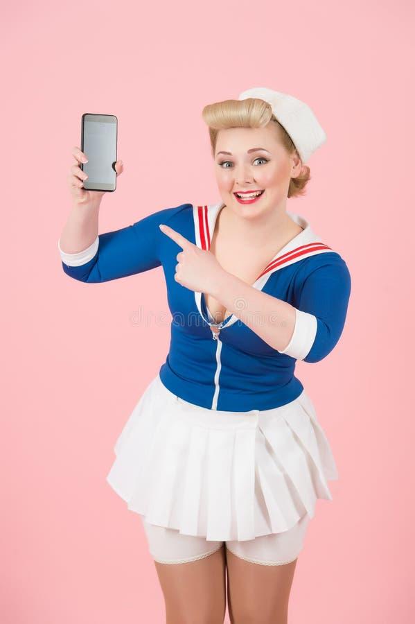 Smart-telefone à disposição da menina retirada do louro do pino-acima A mulher sorrida e feliz propõe olhar no Smart-telefone foto de stock