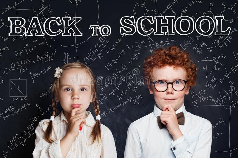 Smart thinking kids boy and girl on blackboard background. Back to school concept stock photo