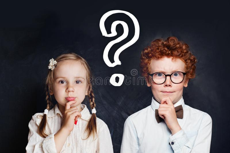 Smart thinking little girl and boy school student with question mark on blackboard background. Brainstorming and idea concept royalty free stock photo