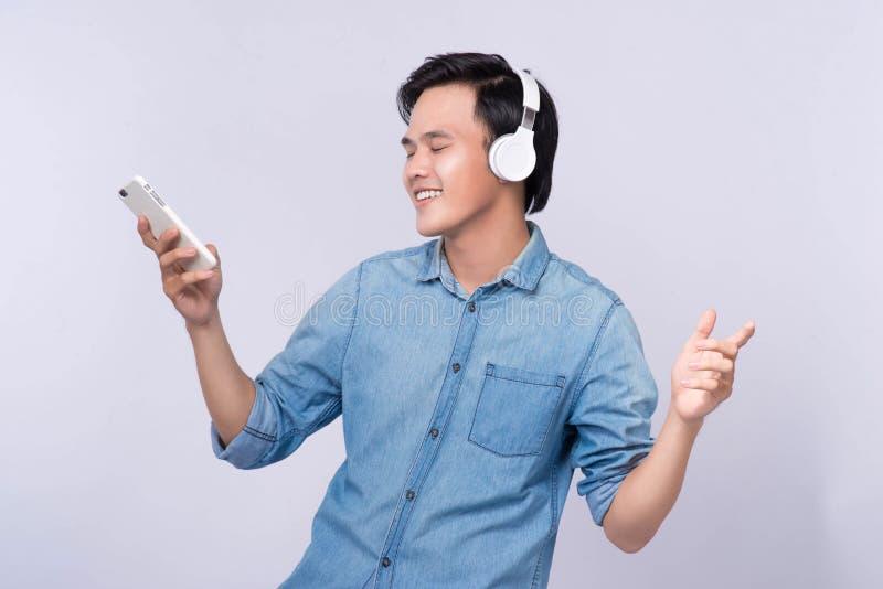 Smart tillfällig asiatisk man som lyssnar till musik i studiobakgrund arkivfoton