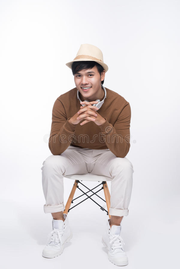 Smart tillfällig asiatisk man som placeras på stol som poserar, medan se awa arkivfoto