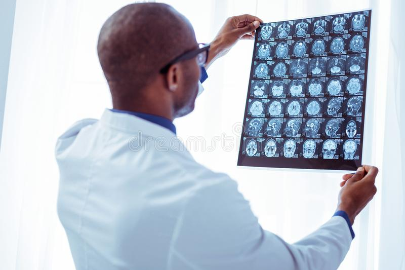 Smart trevlig doktor som kontrollerar en röntgenstrålebild royaltyfria bilder