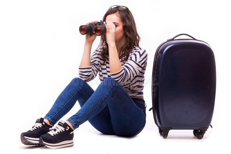 Smart trevlig flickablick över kikare som sitter med hennes stora bagage arkivfoton