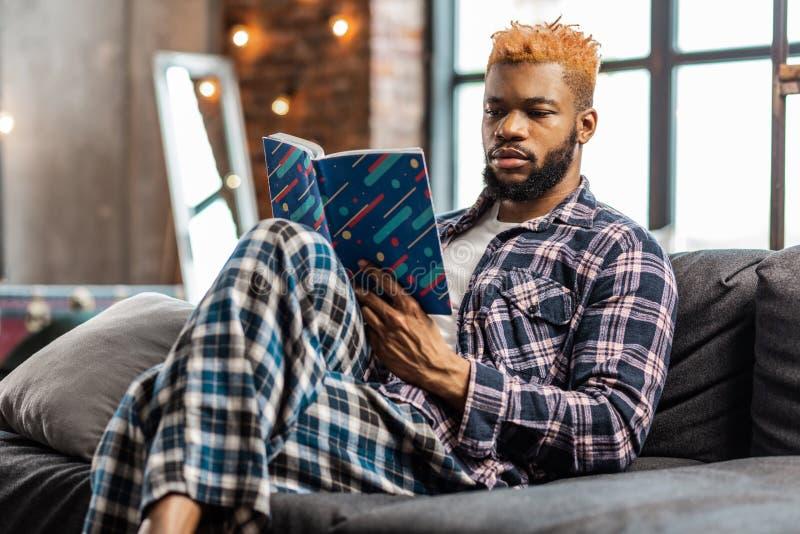 Smart trevlig man som hemma vilar med en bok fotografering för bildbyråer