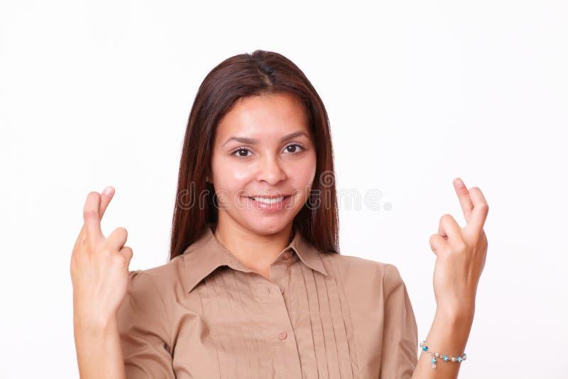 Smart ung dam som korsar henne fingrar royaltyfria bilder