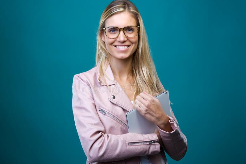 Smart ung kvinna med glasögon som ser kameran, medan rymma den digitala minnestavlan över blå bakgrund royaltyfria bilder