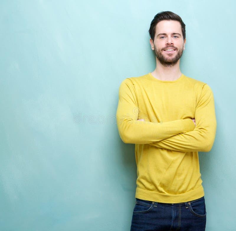 Smart ung man i gul skjorta som ler med korsade armar arkivbilder