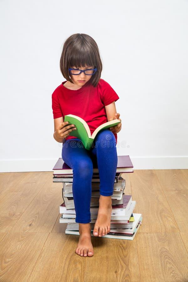 Smart ung primär skolflicka med glasögon som läser för att lära makt arkivbilder