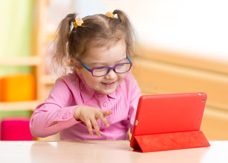 Smart unge i anblickar genom att använda minnestavlaPC eller eBooksammanträde på tabellen i hennes rum arkivbild