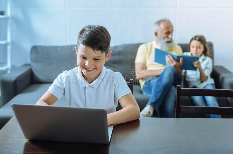 Smart unge som brett grinar, medan arbeta på bärbara datorn arkivbilder