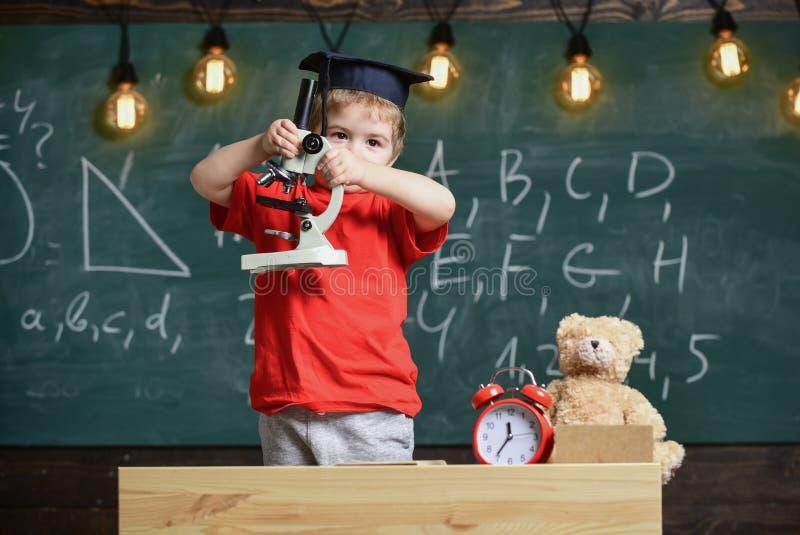 Smart ungebegrepp Första gamla som intresseras, i att studera och att lära, utbildning Barn på upptagen framsida nära mikroskopet arkivbild